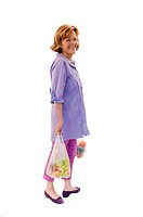 Senior woman holding fruits and vegetables in plastic bag, smiling, portrait (thumbnail)