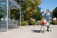 Germany, Munich, Senior woman walking with shopping cart