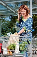 Germany, Munich, Senior woman talking on smart phone while checking her shopping