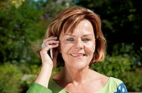 Germany, Munich, Senior woman talking on smart phone, smiling, portrait