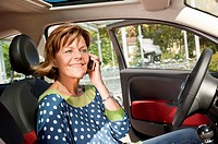Germany, Munich, Senior woman sitting in car and talking on smart phone