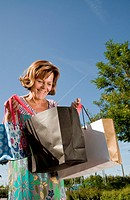 Germany, Munich, Senior woman looking into shopping bag