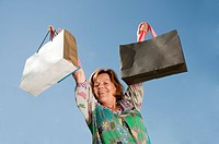 Germany, Munich, Senior woman lifting shopping bag, smiling, portrait
