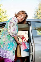 Germany, Munich, Senior woman getting into car with shopping bags