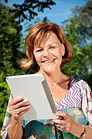 Germany, Munich, Senior woman using digital tablet, close up