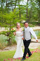 USA, Texas, Bride and groom walking on grass, smiling