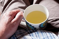 Man suffering with cold holding mug of lemsip in his lap