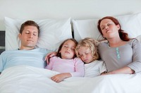 Family sleeping in the bed together