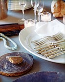 Small group of knives and forks are kept in the plate on the dining table