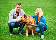 Happy young couple and their German Sheperd sitting in a park