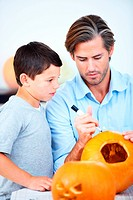 A father helping his young son to make a jack_o_lantern for Halloween