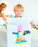 A young boy proudly displays his new watercolour painting for the camera