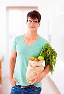 Handsome young hipster holding a bag of fresh groceries