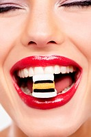 Cropped view of a beautiful young woman eating a liquorice allsort