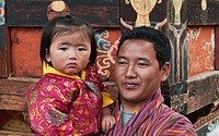 Asia, Bhutan, Bumthang. Man and child watching the Domkhar Tshechu festival. Credit as: Dennis Kirkland / Jaynes Gallery / DanitaDelimont.com