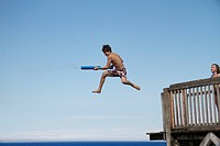 Girl jumping into sea holding water pistol, side view