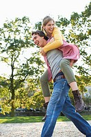Teenage girl having a piggyback ride from young man in park