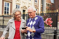 Senior couple using cell phone in city