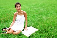 Female Asian student sitting on meadow studying