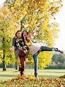 Teenage girls kicking leaves in park