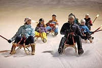 Multigenerational family tobogganing together down ski slope