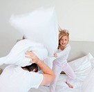 Girl hitting her father with pillow