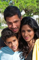Hispanic Spanish family in park outdoors portrait with holding and love