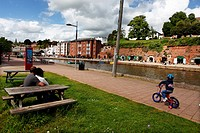 A child cycles on the towpath beside Exeter canal