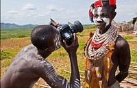Korcho Ethiopia Africa village Lower Omo Valley Karo tribe with painted faces with boy using modern camera taking photos 25