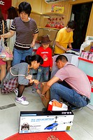 China, Shanghai, Huangpu District, Dianchi Road, small business, man, father, woman, mother, boy, son, wrap box after purchase,