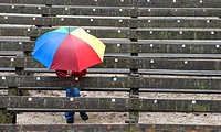 rainy day, lone people with a colored umbrella, wooden bench