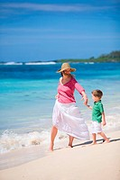 Happy mother and son on white sand tropical beach