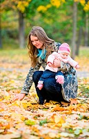 Young mother with daughter enjoying beautiful autumn day