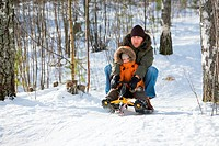 Winter weekend. Father and son sledging on beautiful winter day.