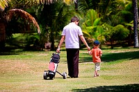 Father teaching his son to play golf.