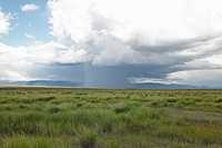 Storm clouds over grasslands and mountains at Red Rock Lake in Centennial Valley, near Lakeview, MT