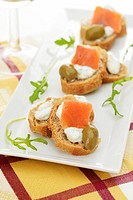Canapes topped with herb cream cheese, smoked salmon and green olives on a rectangular white platter