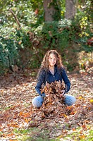 A 24 year old brunette woman throwing leaves in a back yard in the fall