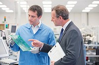 Businessman and engineer examining printed circuit board in manufacturing plant