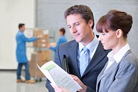 Businessman and businesswoman reviewing paperwork in warehouse