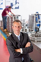 Portrait of serious manager with arms crossed in steel bearing manufacturing plant