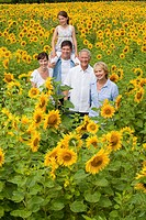 Portrait of smiling multi_generation family among sunflowers in sunny meadow