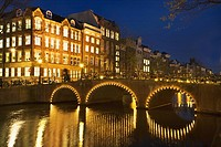 Netherlands, Amsterdam, bicycles on illuminated bridge over Keizergracht Canal at night