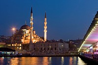 New Mosque illuminated at dusk with fishermen and cafes on the Galata Bridge