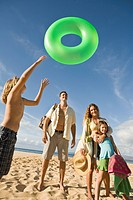 Family at the beach, boy tossing innertube