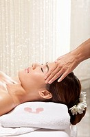 woman receiving facial massage at spa, eyes closed