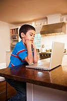 Boy using laptop in kitchen