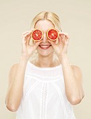 woman holding cut blood oranges over eyes