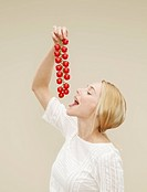 woman holding a bunch of tomatoes to eat