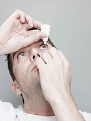 Man Inserting Eye Drops Into Eye.